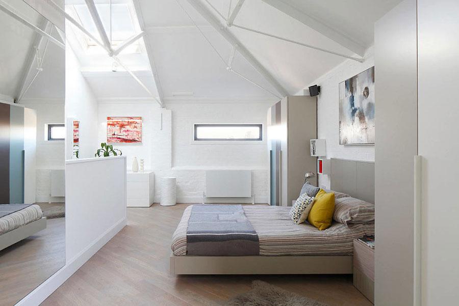 Stoere zolderslaapkamer met wit geschilderde bakstenen