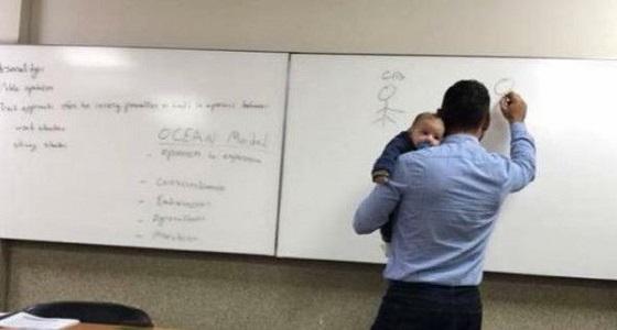 صورة أستاذ جامعي يحمل طفلاً بالمحاضرة تسرق القلوب