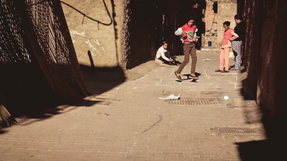 children playing hopscotch in an alleyway