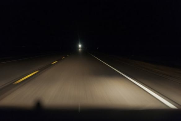 """""""A Lonely Coast"""" involves a dark highway drive along a dark highway such as this"""