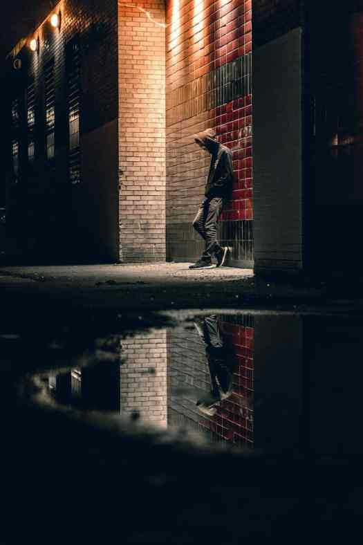 man in hoodie at night with his reflection in puddle
