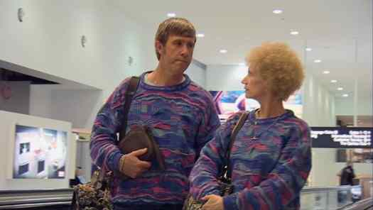 Despite their loud jumpers, Kath and Kel are structurally invisible during their tourist experience at the airport.