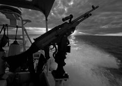 "A side mounted SAW ""machine gun"" is at the ready at members of a US Coast Guard security detail, in a Viper fast boat, patrol the waters of Guantanamo Bay, Cuba 23 April 2007 at sunset."