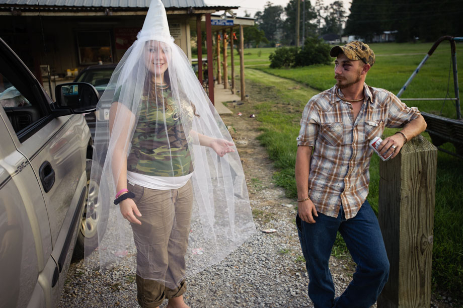 """Little Charlie"" of the Dixie Rangers of the Ku Klux Klan displays her custom made wedding veil, as her fiancée watches on."