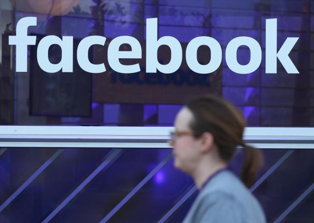 512015586-woman-walks-past-the-facebook-logo-at-the-facebook