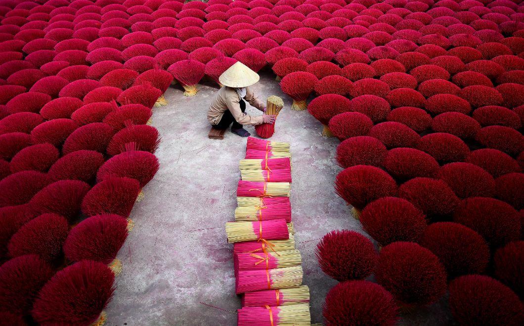 Cette photo, prise le 3 janvier 2019, montre une Vietnamienne ramassant des bâtons d'encens dans une cour du village de Quang Phu Cau, à la périphérie de Hanoï. Dans cette petite ville, considéréecomme le village de l'encens, des centaines de travailleurs et de travailleuses sèchent et taillent l'écorce de bambou pour fabriquer ces bâtonnets parfumés avant les vacances du Nouvel an lunaire.
