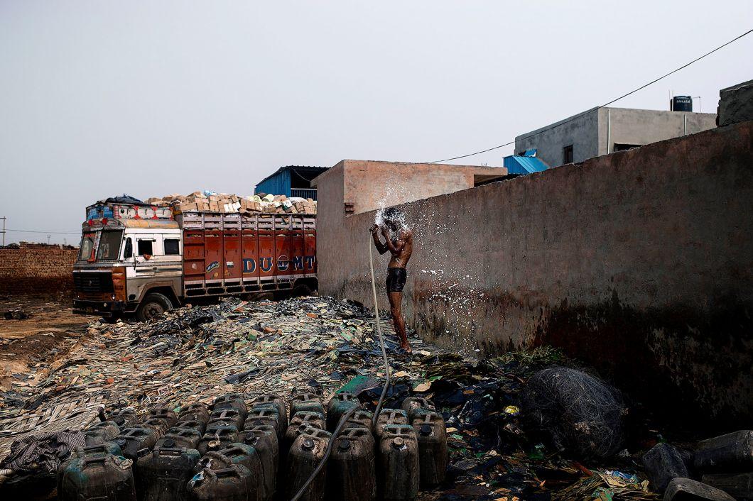 «Cette décharge est situéeà l'extérieur de Delhi. Un homme se tient debout sur une montagne de vieux circuits imprimés. Il se lave le corps après une journée de travail épuisante. Devant lui, des cartes de circuits imprimés sont trempées dans des jerricans en plastique remplis d'acide pour extraire le cuivre par un procédé extrêmement dangereux.À l'arrière, un camion vient d' arriver avec de nouveaux déchets.»