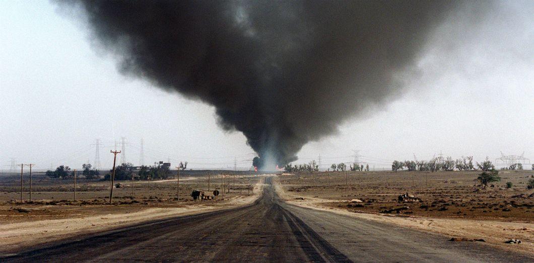 Un puit de pétrole enflammé par les forces irakiennes, lors de leur retraite du Koweit en 1991. | Michel Gangne / AFP