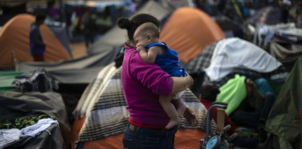 Une mère porte son bébé dans un camp à Tijuana, au Mexique, près de la frontière américaine, le 28 novembre 2018. | Pedro Pardo / AFP