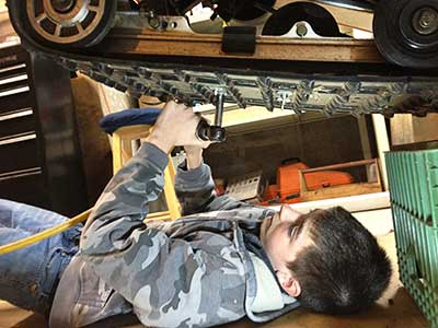 Father and Son Snowmobile Project studding a track
