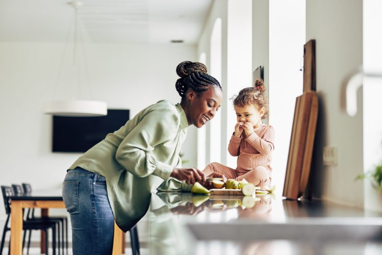 Smiling young African mom and her adorable little girl enjoying a healthy fruit snack together in their kitchen at home