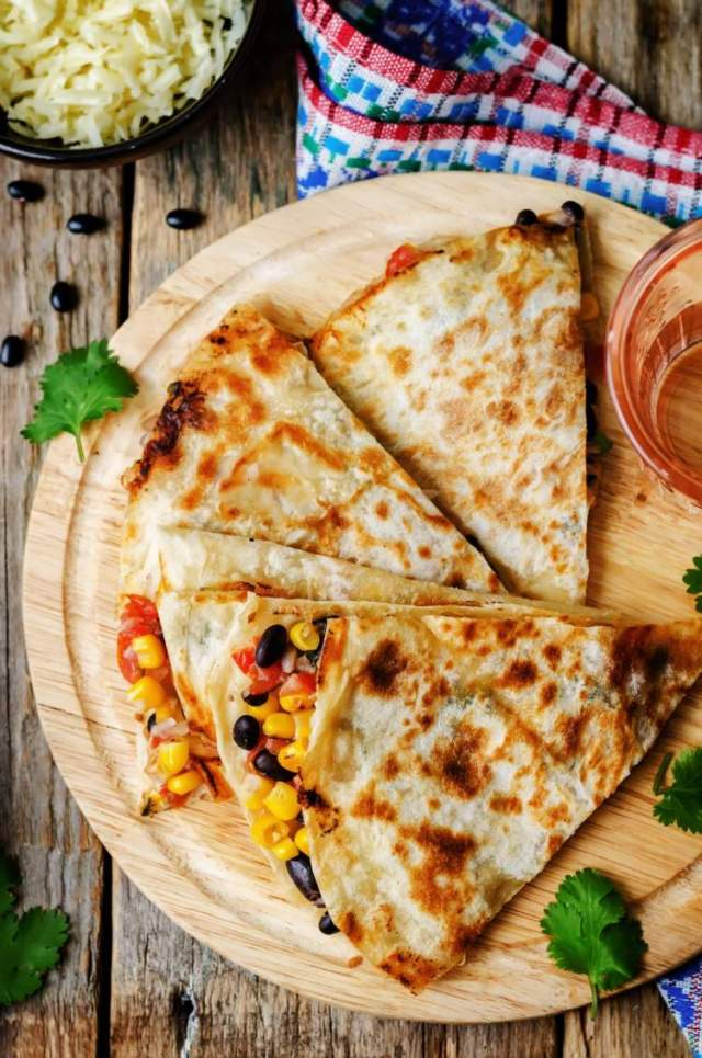 Black Bean and Corn Quesadilla on a wooden cutting board with salsa.
