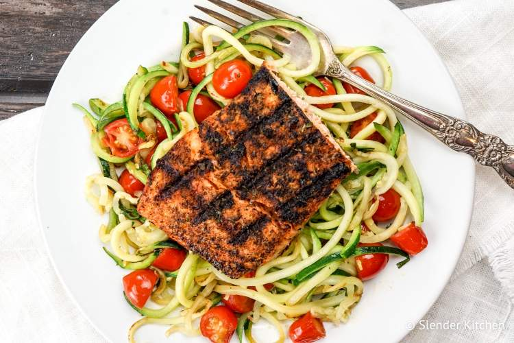 Blackened Salmon with Garlic Zucchini Noodles on a white plate and wooden background.