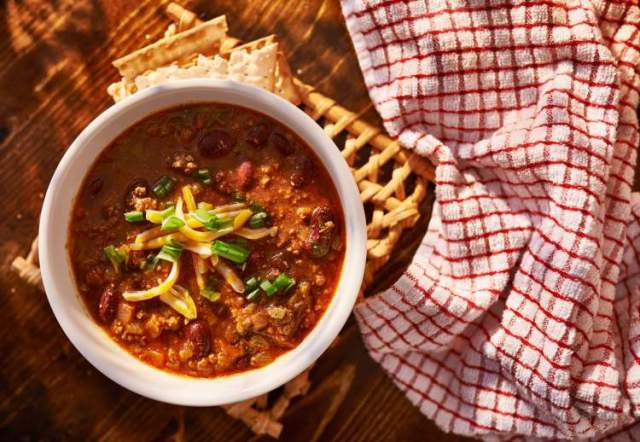 Easy Beef chili recipe in a bowl with a checkered napkin and crackers..