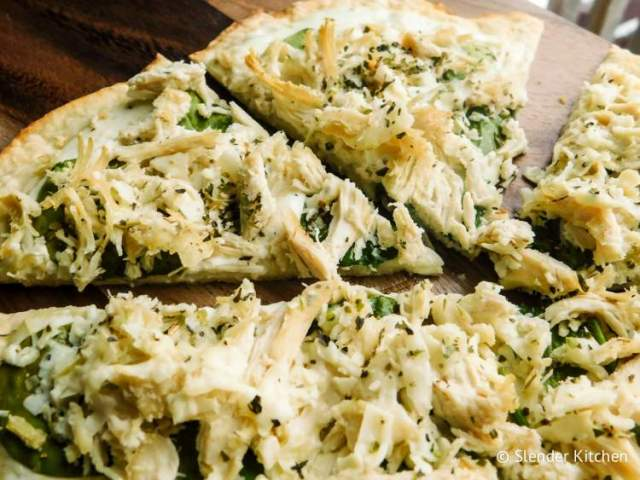 Skinny Chicken Alfredo Pizza on a wooden table with melted cheese.