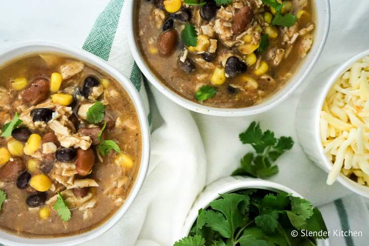 Slow Cooker Weight Watchers Taco Soup with cilantro, cheese, and baked tortilla chips.