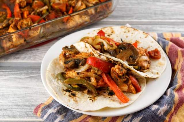 Baked Chicken Fajitas in two flour tortillas with pepeprs and onions.