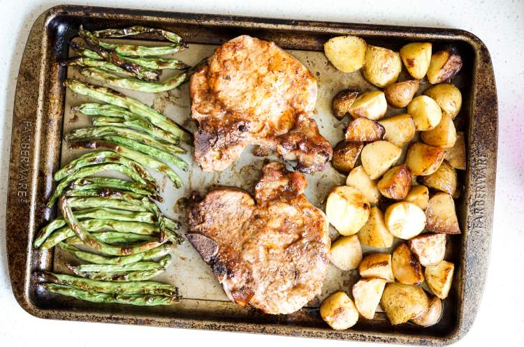 Pork chops, green beans, and potatoes all on a sheet pan.