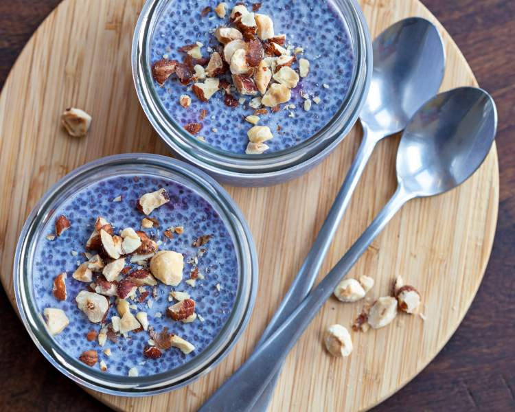 Two containers light Blue chia pudding on a wooden bar with a spoon.