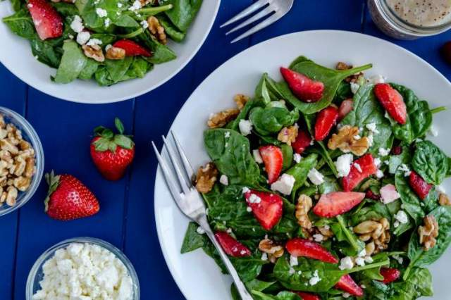 Strawberry spinach salad with feta cheese and walnuts on a blue table.