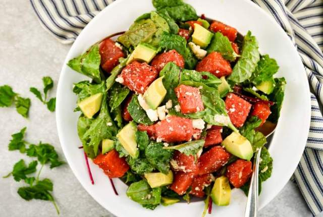 Watermelon and Avocado Salad in a bowl with a spoon and white napkin..