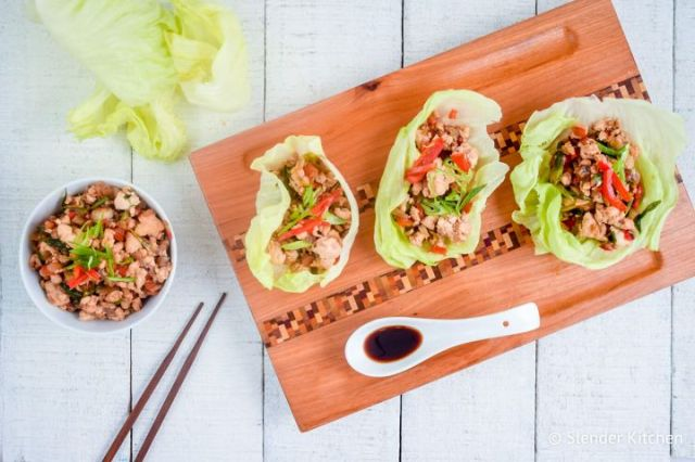 Chicken lettuce wraps on a wooden board with ground chicken and veggies in a hoisin sauce.