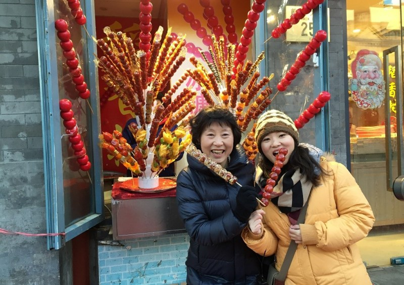 my auntie Yuanhui and I eating candied hawthorn fruit