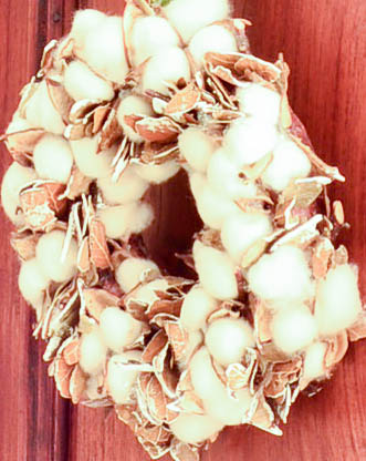 Cotton Wreath on a French Armoire hung with a ribbon