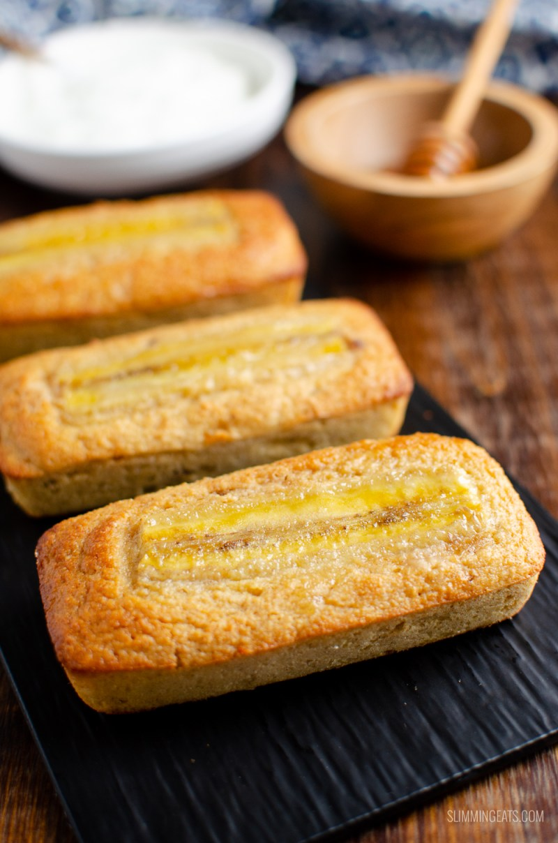 low syn mini banana raisin loaf on black tray with yoghurt and honey