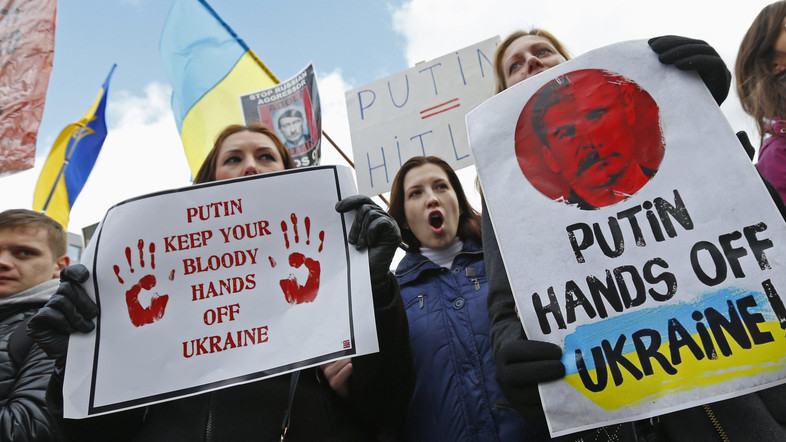 People protesting against Russian troops in Ukraine gather outside an European Union emergency foreign ministers meeting in Brussels