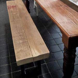 Bank van oude balken en stalen o-onderstel voor tafel