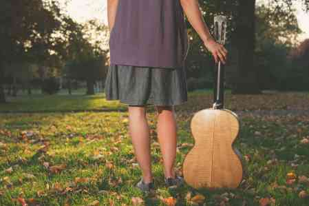 Woman with guitar at sunset in the park
