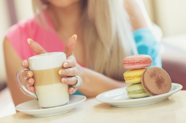 A hot Cup of coffee latte with colorful sculpture cookies