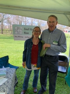 Woman with long hair standing next to taller man, both middle ages, both wearing glasses, standing in front of a banner that says Small Garden News.