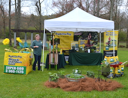 White tent, table covered with green cloth, and bright yellow bags of Soil3 artfully displayed.