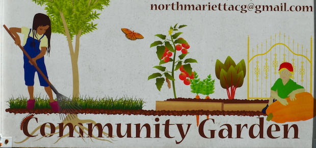 Sign for a community garden with painted images of children working in a garden, tomato plant, a pumpkin, carrots growing, a tree, and a butterfly