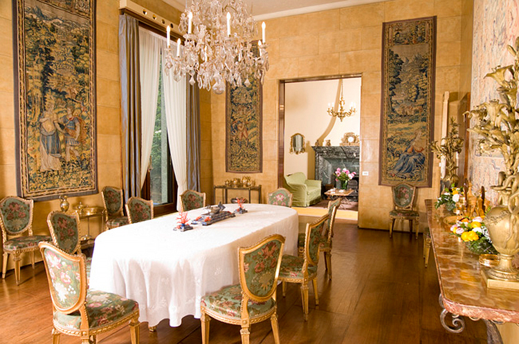 (above) The dining room with the former owners' design choices. Fortunately the film set designers chose to cover those chairs and strip most of the tapestries from the walls.