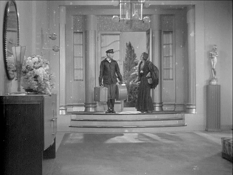 (above) His home. The use of steps dropping from the front door entrance into the foyer is a common architectural feature used in films of the 1930s and 40s.