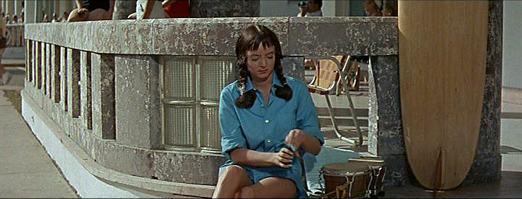 (above) Carolyn wearing beatnik casual was filmed on location at the Cardozo Hotel on Ocean Drive.  Two things that would seem out of place today are the bongos and wooden surfboard.