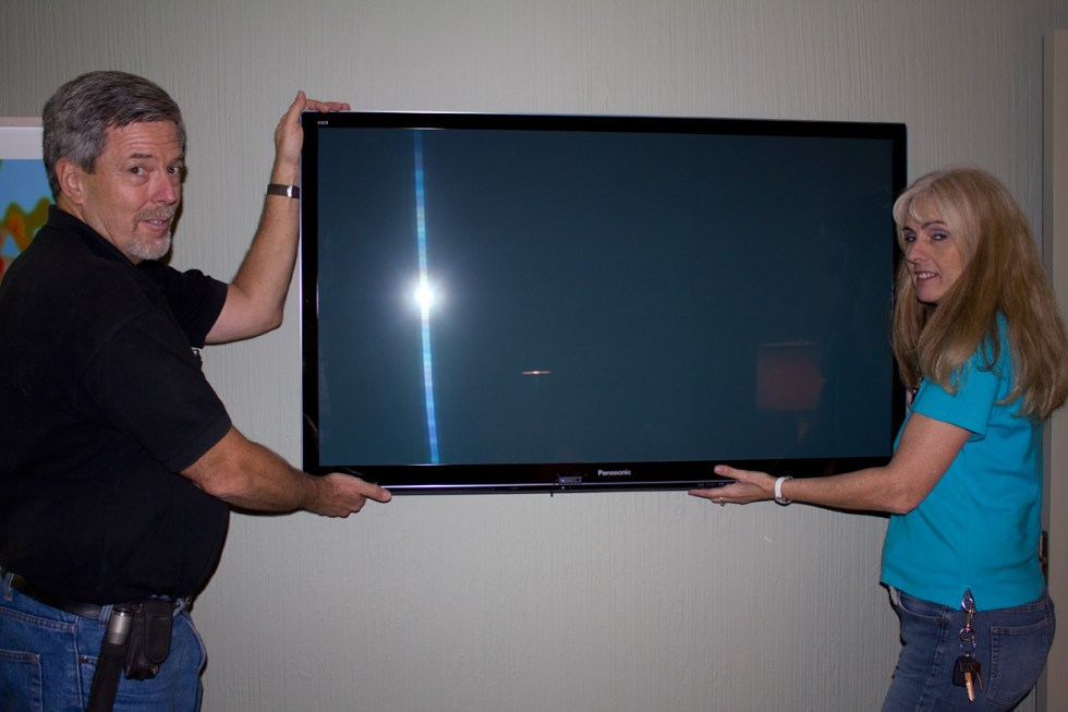 (above) Topp Robertson of M31 Inc. with his wife and partner Shannon set up my two flat screen televisions with a combination of hard wiring to the computer and wireless. Both sets of cable boxes and dvd players are now hidden inside a closet or cabinet and can be controlled with a remote pointed toward a button attached to the front of each display.