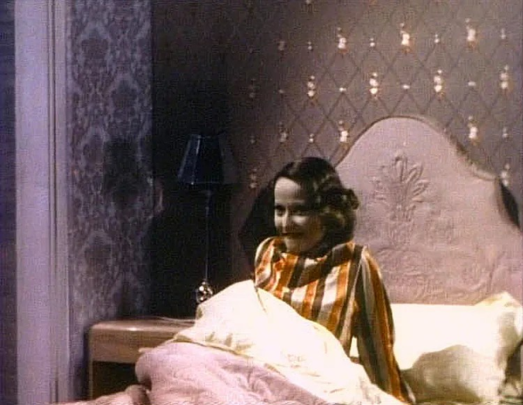 (above) Notice that the wall covering behind the headboard has shiny gold thingies. Even her pajama's color combination coordinates with her surroundings.