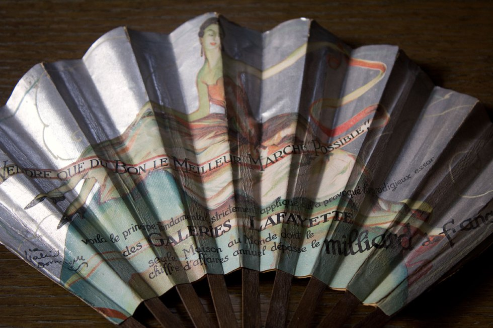 "(above) The back side of the above fan is signed by a different artist and appears to be an ad for Galleries Lafayette. In tiny letters on the right edge are the words ""Made in France 1926."""