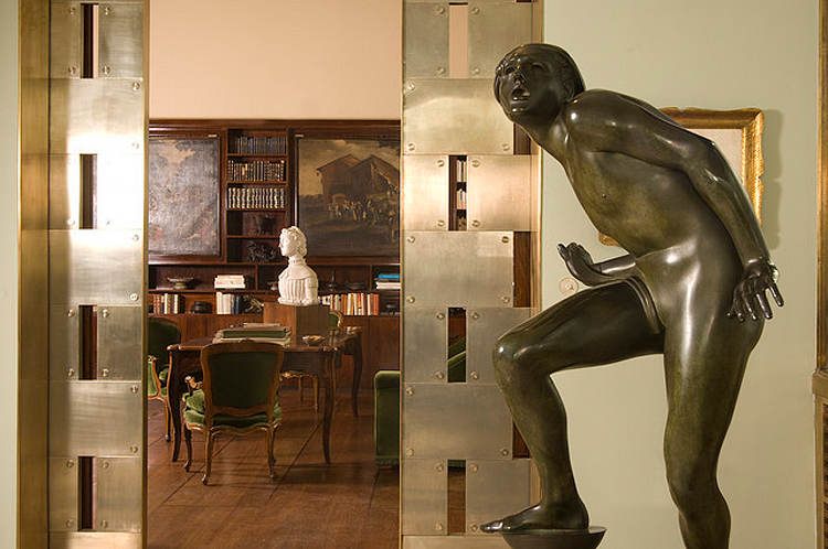 (above) detailed view of the metal pocket door that separates the veranda from the library. In the foreground, Adolf Wildt, 'The Pure Lunatic,' 1930, bronze. (photo by Giorgio Majno)[
