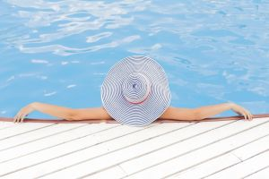 A woman with a hat relaxing in a pool.