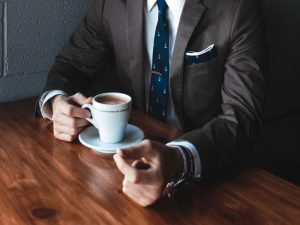 A businessman in a suit drinking coffee.