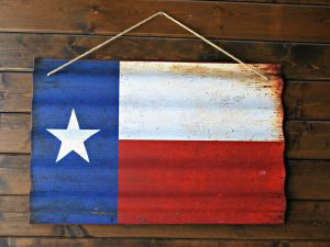 A Texas flag painted on a piece of wood, hanging on a wall.