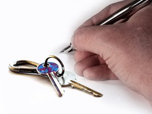 Hand holding a pen ready to sign something, keys left of it