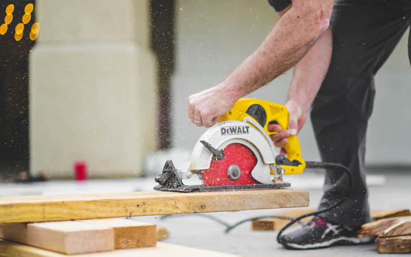 a married man wearing Asics shoes is using a DeWalt skill saw