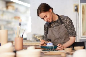 A woman paints a ceramic bowl.