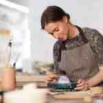 A woman paints a ceramic bowl.